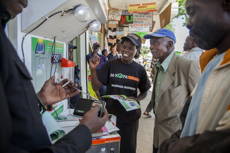 M-KOPA Sales lady describing product to man