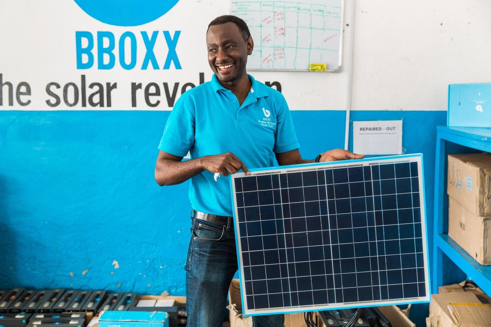 BBOXX employee holding solar panel