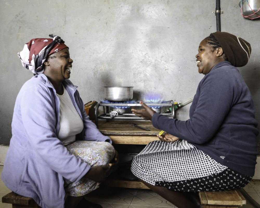Two African ladies talking whilst sitting next to gas stove cooking