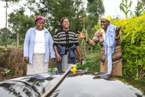 Africa: man showing two ladies biodigester system