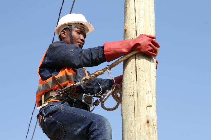 African man climbing a wooden pole