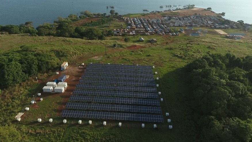 Overhead image of solar plant and African village in background