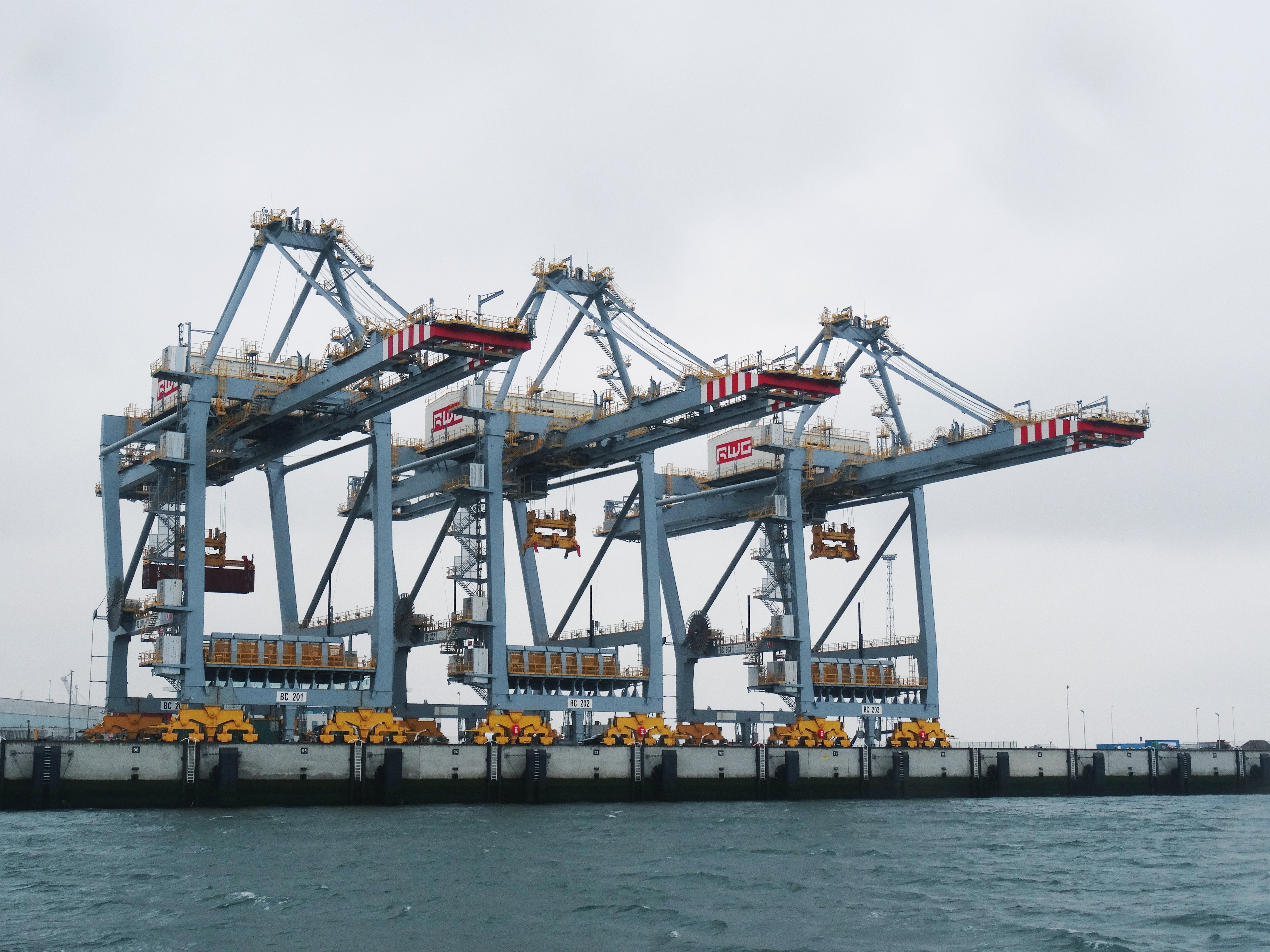 Three large freight cranes on the docks next to sea