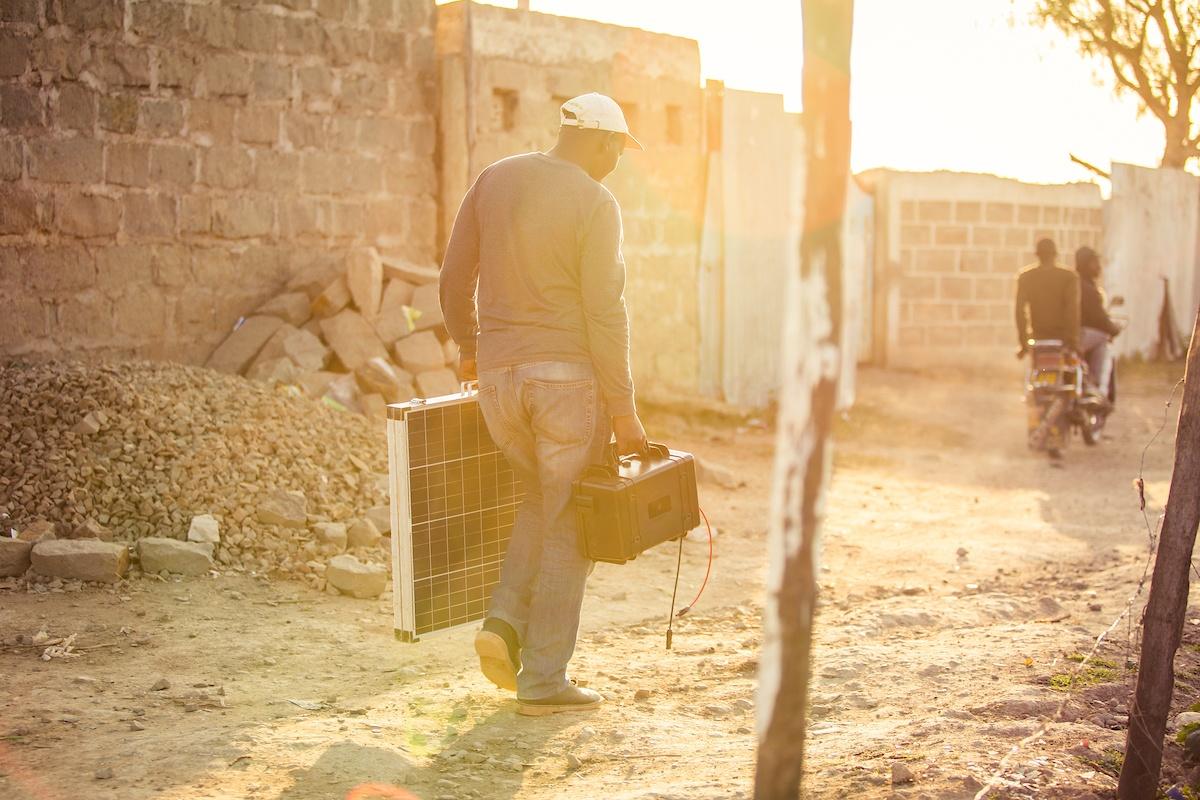 Man carrying solar kit through African village