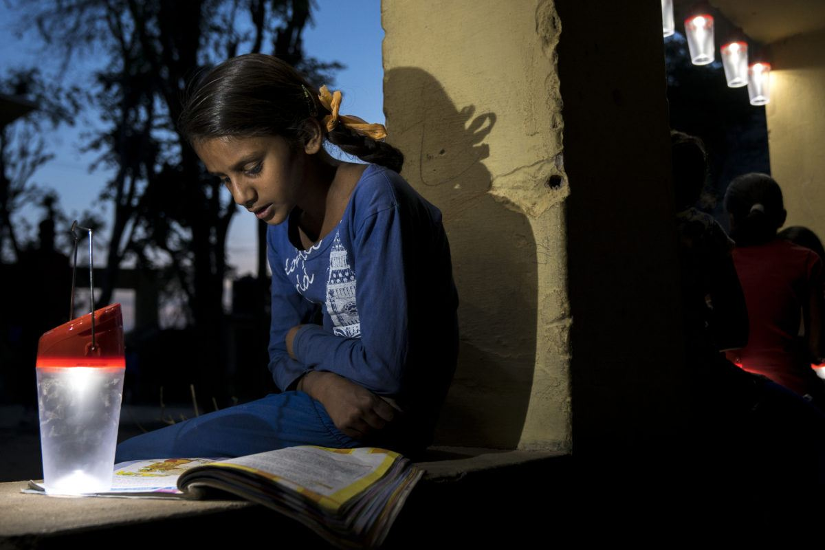 Young Indian girl reading by solar lantern