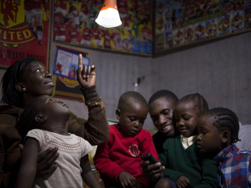 African family in room with solar light above