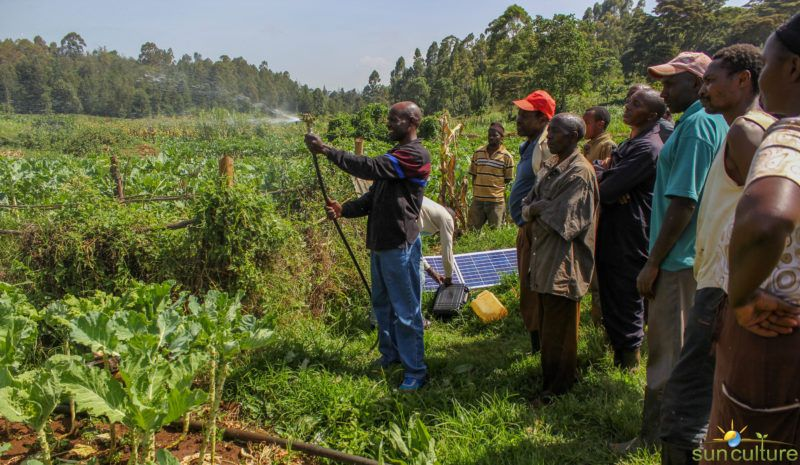 African man showing group a oslar powered irrigation system in the field