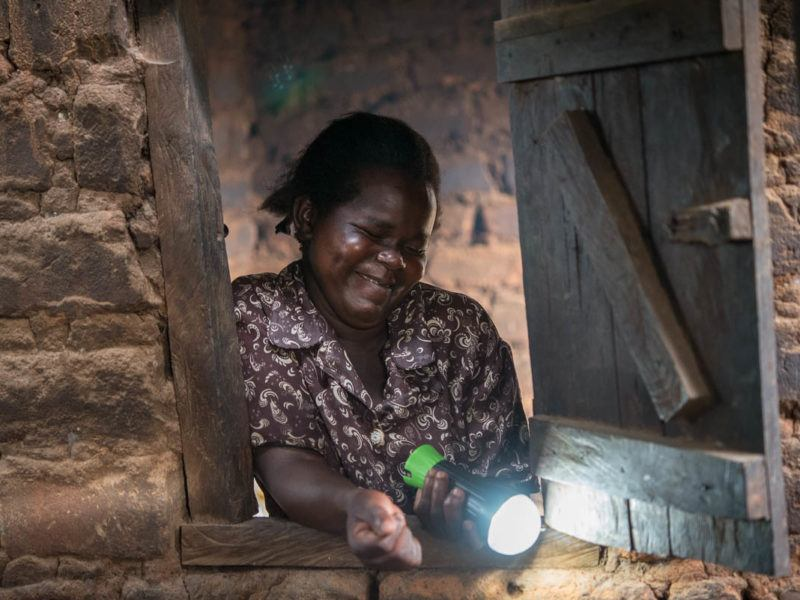 African lady shining solar torch through window opening