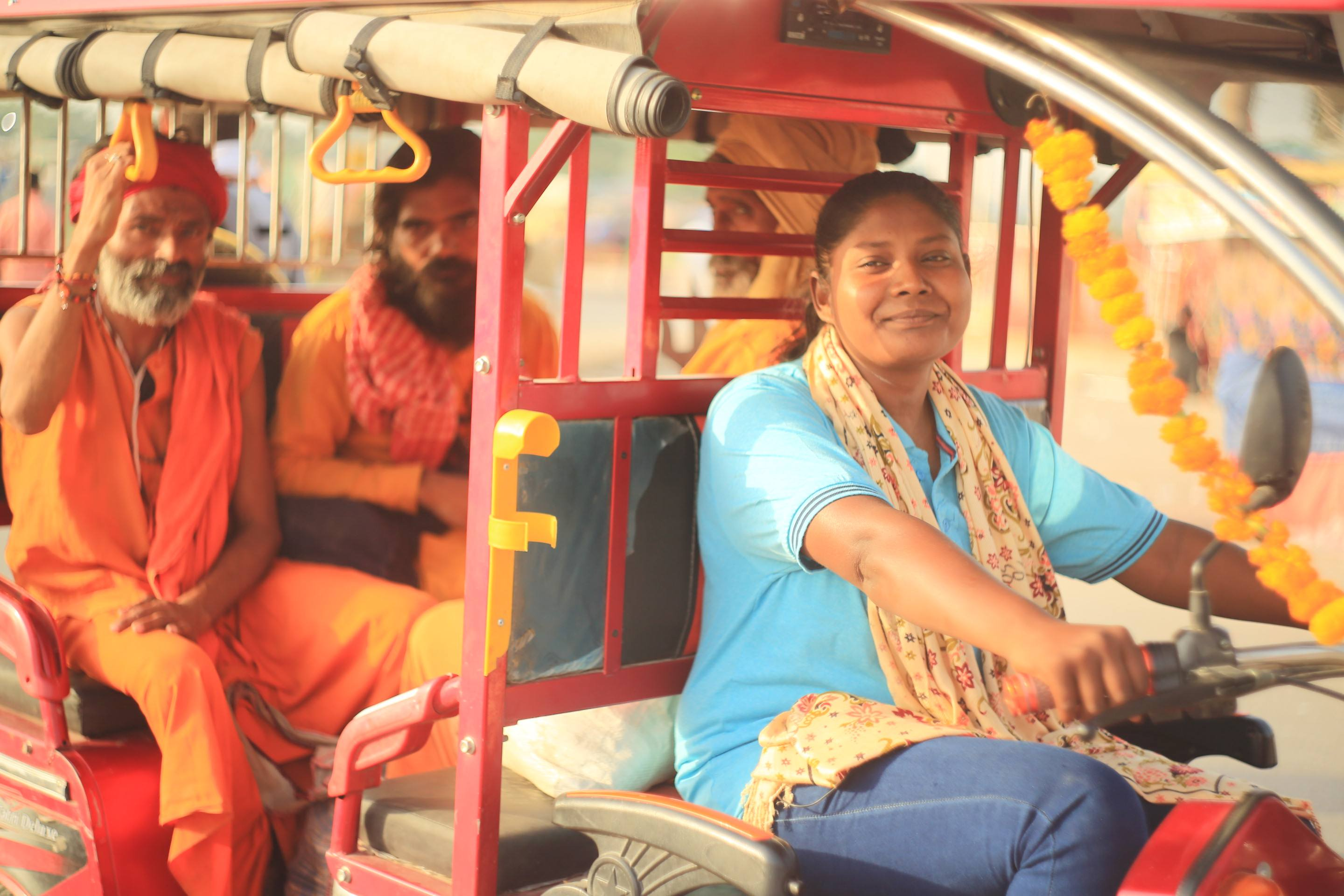 Indian lady driving tuk tuk with two male passengers