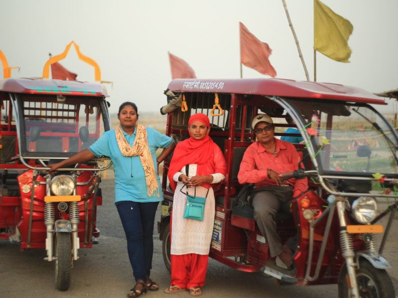 Three female e-rickshaw drivers in front of their rickshaws