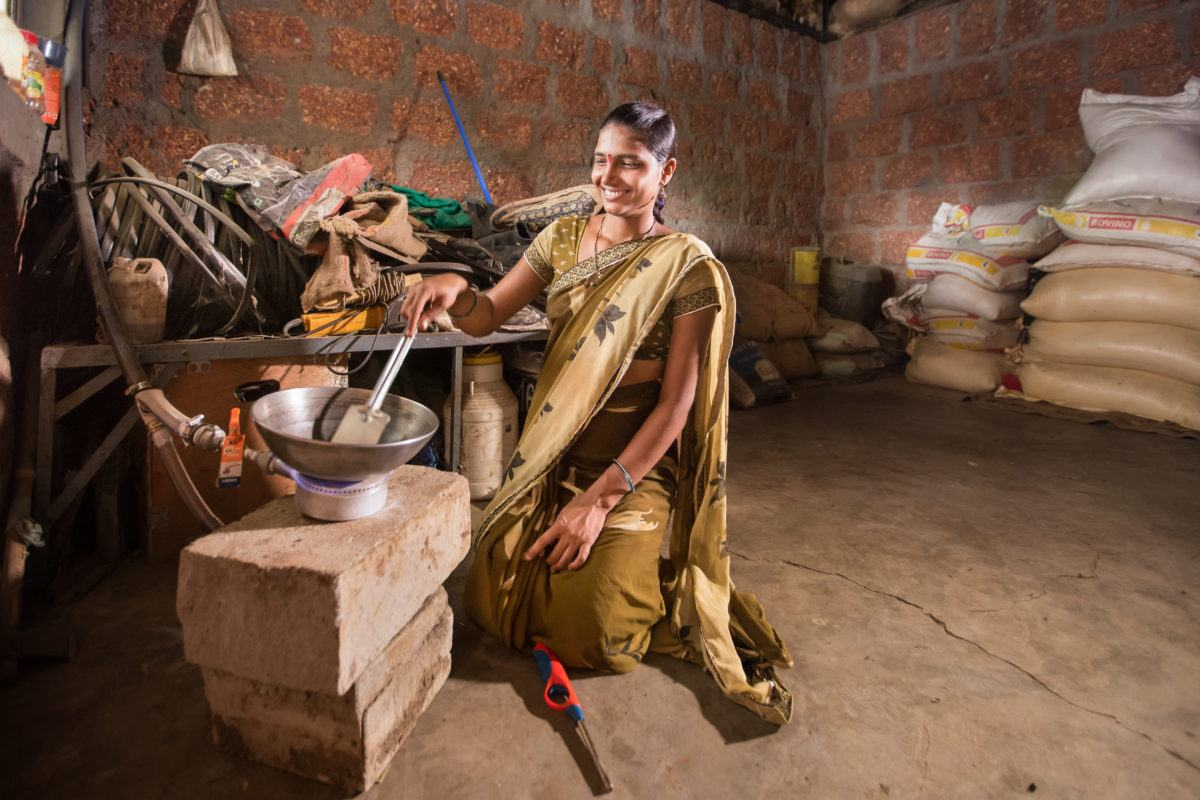Indian lady cooking in kitchen on gas stove