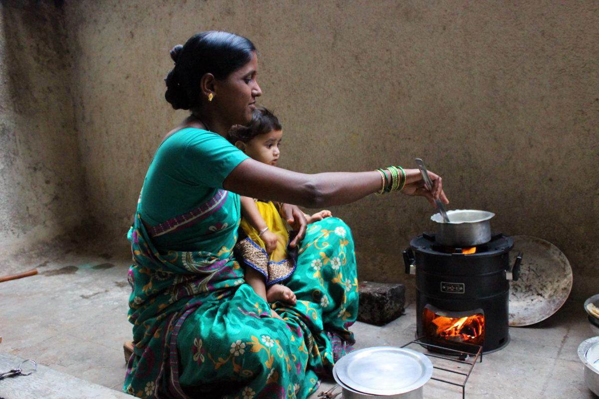Indian lady sitting cross legged with child on lap cooking on Envirofit stove