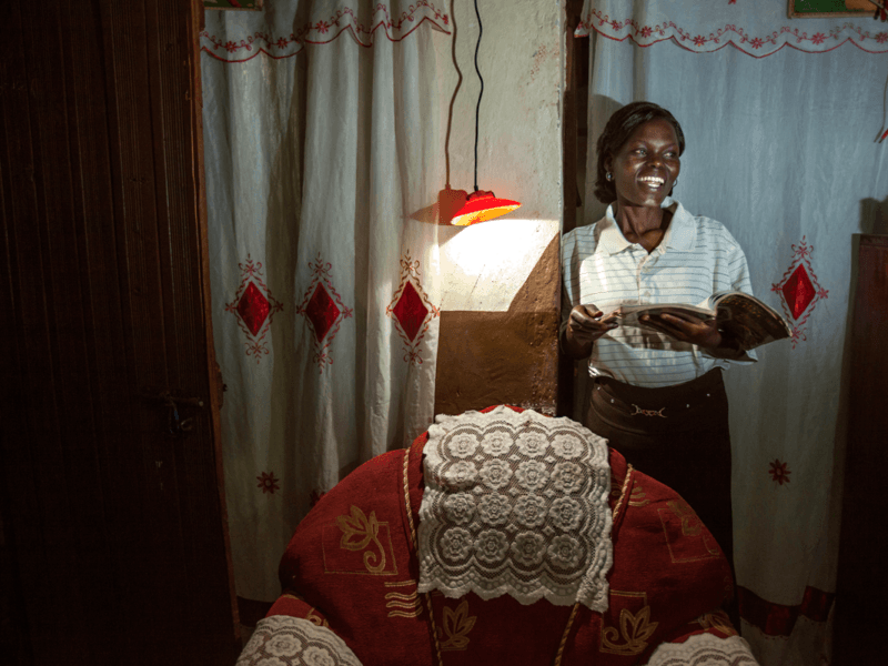 lady standing reading by solar light - Africa