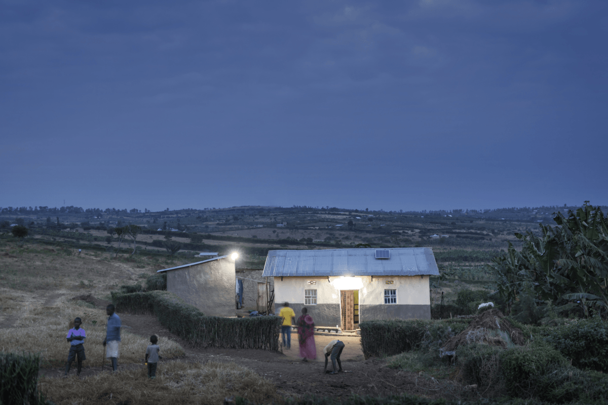 Solar lit house at dusk in village with people