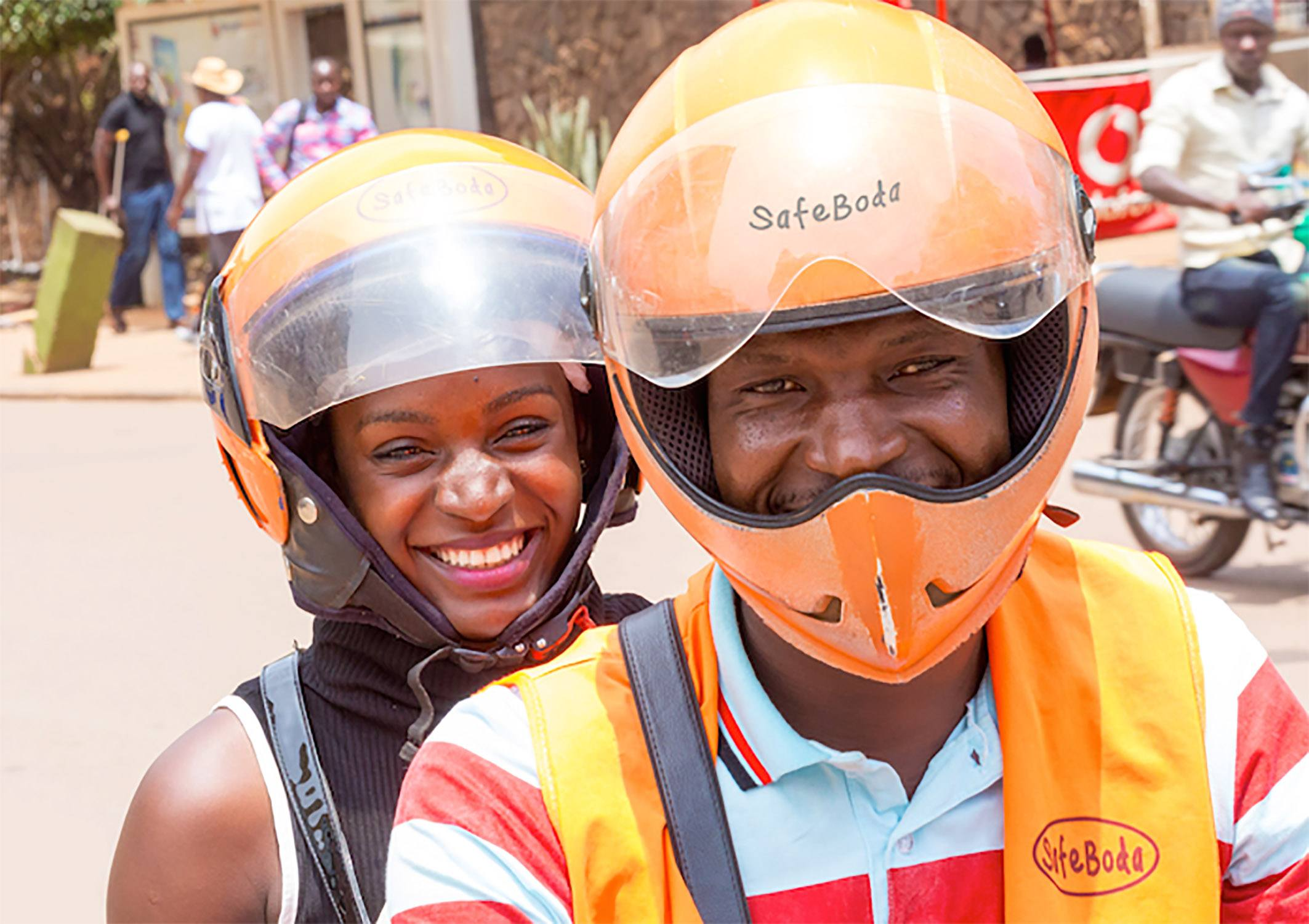 SafeBoda motorcycle rider with lady passenger on back