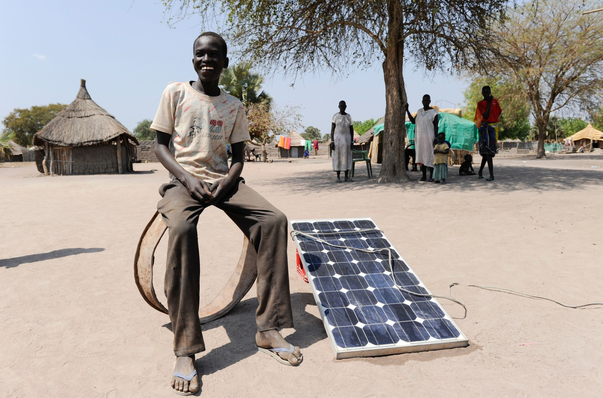 Young African man sitting on some sort of ring next to a solar panel